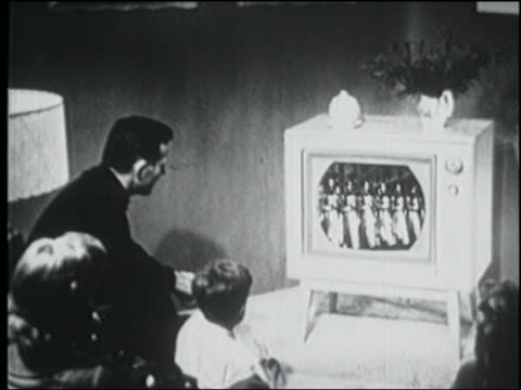B/W 1956 high angle REAR VIEW family sitting in living room watching marching soldiers on television