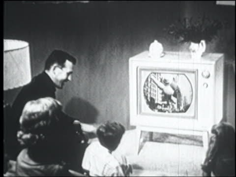 B/W 1956 high angle REAR VIEW family sitting in living room watching parade on television