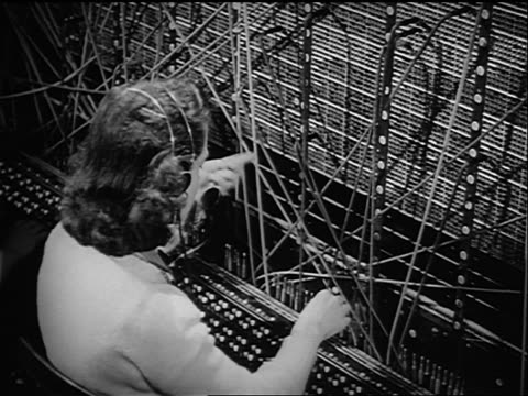 b/w 1946 high angle rear view female telephone operator plugging cables into switchboard - カスタマーサービス担当者点の映像素材/bロール