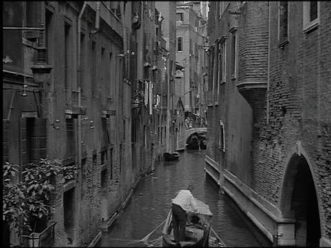 B/W 1930 high angle REAR VIEW gondolier pushing gondola on narrow canal between buildings / Venice