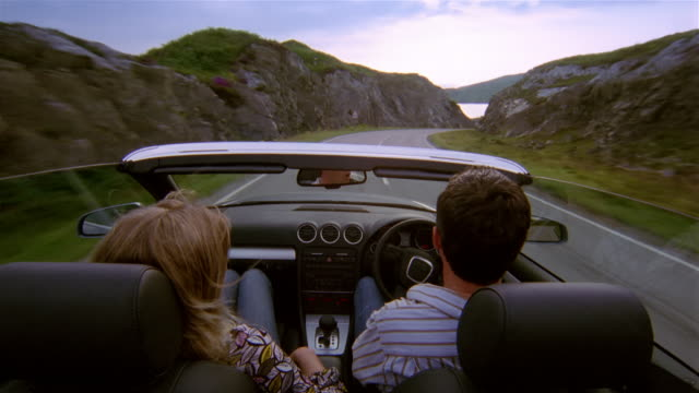 High angle rear view man and woman driving in convertible along curving mountain road / Scotland