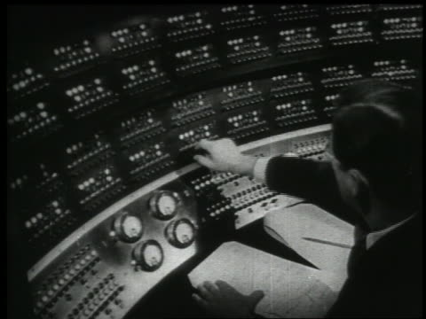 b/w 1938 high angle rear view man in control room of radio studio - radio studio stock videos & royalty-free footage