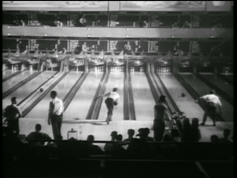 vídeos de stock, filmes e b-roll de b/w 1938 high angle rear view men throwing bowling balls down lanes of bowling alley in tournament - cancha de jogo de boliche