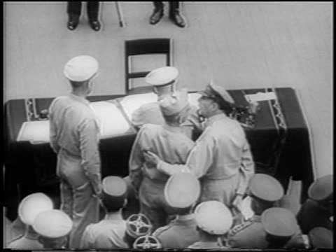b/w 1945 high angle rear view nimitz sits at table / officers in background / surrender of japan on uss missouri - william halsey stock-videos und b-roll-filmmaterial