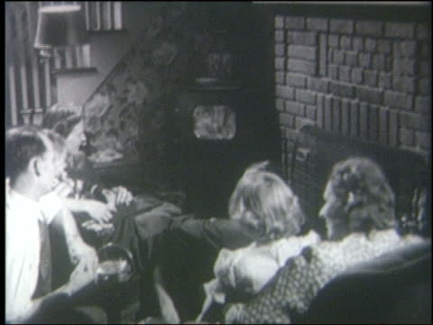 b/w 1950 high angle rear view over-the-shoulder family sitting in living room watching television - anno 1950 video stock e b–roll
