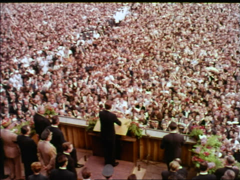 1963 high angle rear view president john kennedy at podium making speech to cheering crowd / berlin - john f. kennedy politik stock-videos und b-roll-filmmaterial