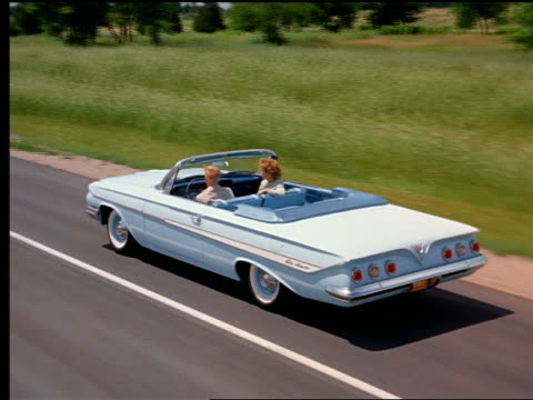 1961 high angle REAR VIEW tracking shot couple driving in blue Chevrolet Impala convertible on country highway