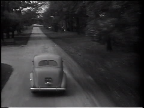 B/W 1937 high angle REAR VIEW tracking shot Ford V-8 car driving on road past houses / commercial