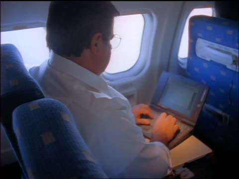 high angle rear view zoom in man in eyeglasses sitting in airplane typing on laptop - abitacolo video stock e b–roll