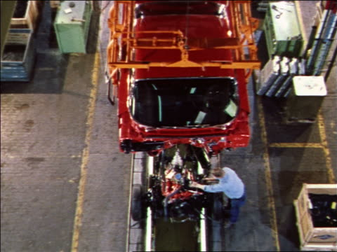 1959 high angle red car body being lowered to men assembling car on assembly line below / 1960 Chevy