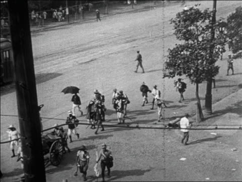 vídeos de stock, filmes e b-roll de b/w 1923 high angle refugees walking on street after earthquake in tokyo / newsreel - 1923
