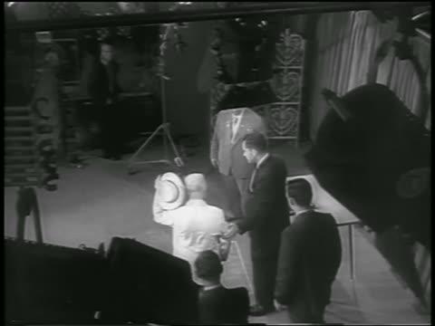 B/W 1959 high angle Richard Nixon Nikita Khrushchev other man posing under lights in room