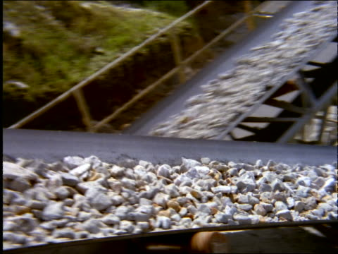 high angle pan of rocks moving on sloped conveyor belt outdoors / brazil - natural phenomena stock videos & royalty-free footage