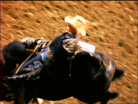 high angle rodeo rider on bucking bull coming out of chute / falls off + clown runs in - bucking bronco stock videos & royalty-free footage