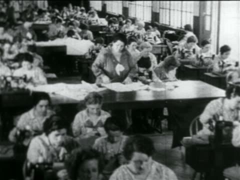 b/w 1934 high angle room full of women using sewing machines in wpa garment factory / documentary - 雇用促進局点の映像素材/bロール