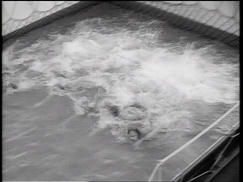 b/w 1934 high angle pan row of girls racing in swimming pool on ship deck / cruise ship - 1934 stock videos & royalty-free footage