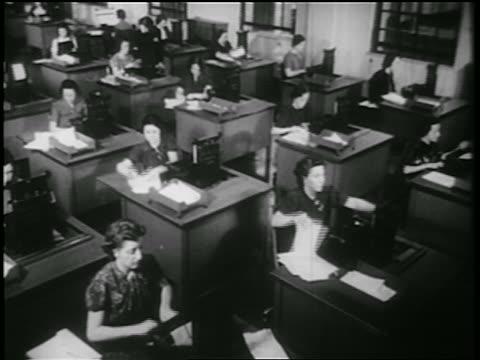 vídeos y material grabado en eventos de stock de b/w 1939 high angle rows of women using adding machines at desks in office / documentary - secretaria