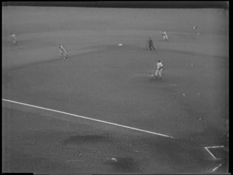 high angle sal maglie pitches, jackie robinson bats + runs to first base, pee wee reese runs home - 1951点の映像素材/bロール