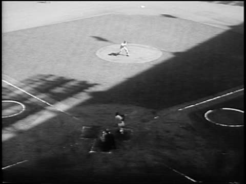 stockvideo's en b-roll-footage met b/w 1956 high angle pan sal maglie pitching to mickey mantle who hits a home run in world series - 1956