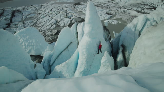high angle scenic view of ice climber approaching peak of glacier using hooks / palmer, alaska, united states - 上がる点の映像素材/bロール