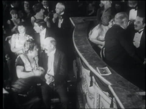 B/W 1922 high angle seated audience in formalwear clapping in theater / man in balcony points