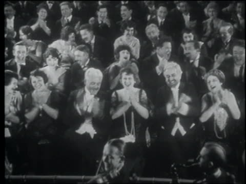 vidéos et rushes de b/w 1922 high angle seated audience in formalwear clapping - applaudir