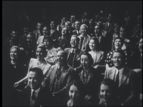 B/W 1947 high angle seated audience laughing in theater / documentary