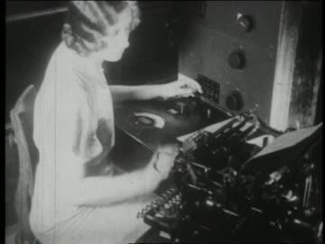 b/w 1930 high angle secretary typing + using early telephone technology - 1930 bildbanksvideor och videomaterial från bakom kulisserna