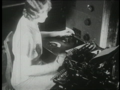 b/w 1930 high angle secretary typing + using early telephone technology - 1930 stock-videos und b-roll-filmmaterial