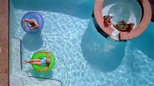High angle senior couple floating on inner tubes in swimming pool and senior couple sitting in whirlpool