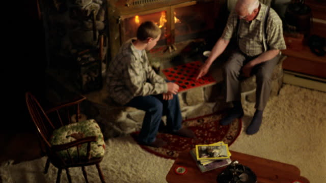 high angle senior man and boy playing checkers by fireplace - draughts stock videos & royalty-free footage