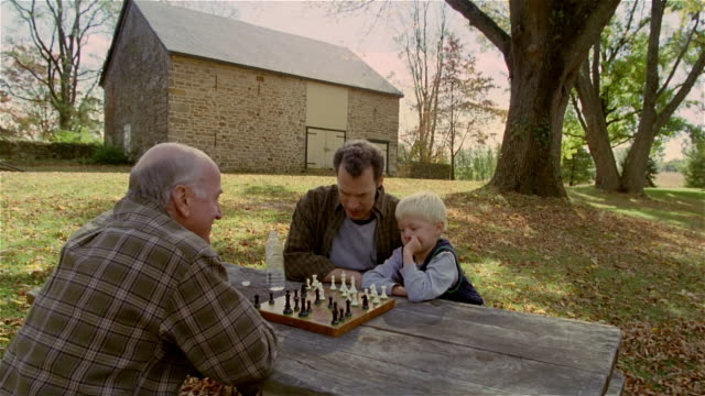 high angle senior man playing chess against mature man and young boy outdoors / autumn - grandfather stock videos & royalty-free footage