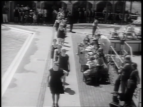 B/W 1939 high angle senior women with bathing suits walking in line by swimming pool in senior beauty pageant