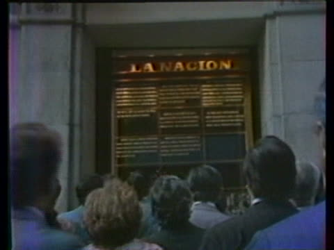 high angle shot crowd of people reading headlines on exterior wall people reading la nacion headlines from behind - buenos aires stock videos & royalty-free footage