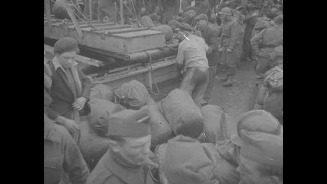 high angle shot mass of french soldiers, with backpacks and rolls full of gear, waiting to board ship to be deployed / several of the soldiers / vs... - hochziehen stock-videos und b-roll-filmmaterial