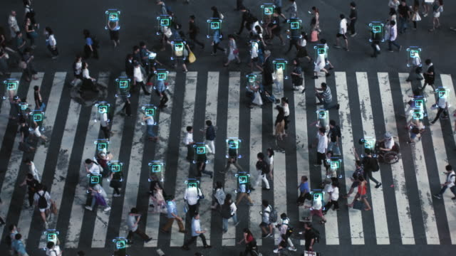 High Angle Shot of a Crowded Pedestrian Crossing in Big City. Augmented Reality Shows Visual Representation of Face Recognition Technology. Artificial Intelligence Learning Process.