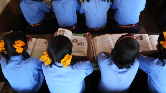 High angle shot of a group of young schoolgirls who are reading a book at their desk during class in a school in the village Satia a small settlement...