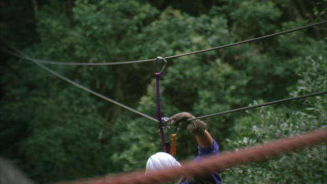 High angle shot of a man on a canopy tour or canopy zip lining to a platform