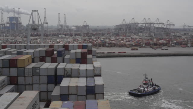 vidéos et rushes de high angle shot of a pilot boat guiding a container ship into the port of rotterdam. - remorqueur