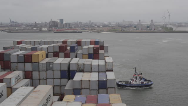 high angle shot of a pilot boat guiding a container ship into the port of rotterdam. - rotterdam stock videos and b-roll footage