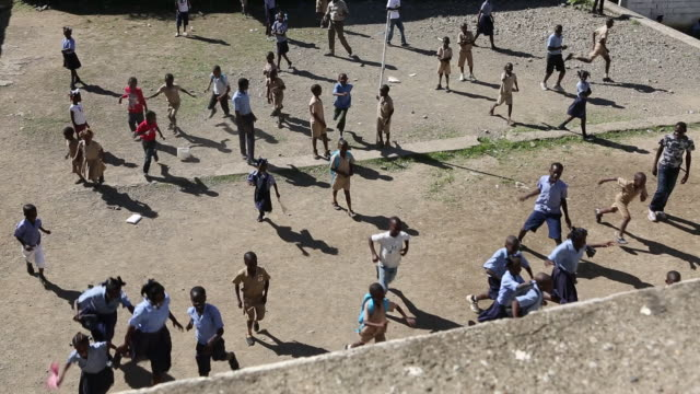 vidéos et rushes de a high angle shot of a schoolyard full with primaryschool pupils who are playing with each other and running down the playground as the camera is... - antilles occidentales
