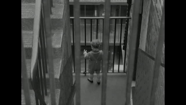 High angle shot of a small boy peering through railings in a tenement building