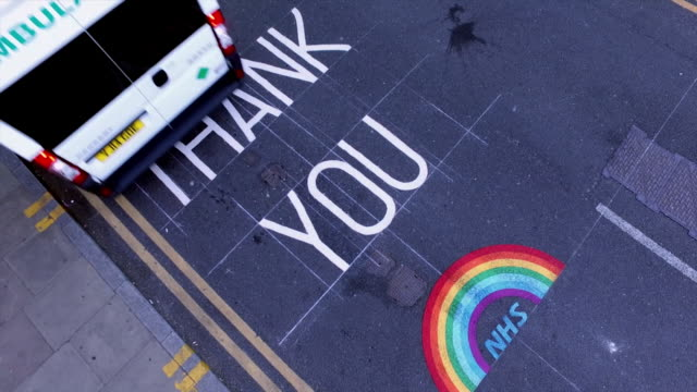 high angle shot of ambulance driving over thank you nhs and rainbow sign painted onto tarmac outside hospital - shape stock videos & royalty-free footage
