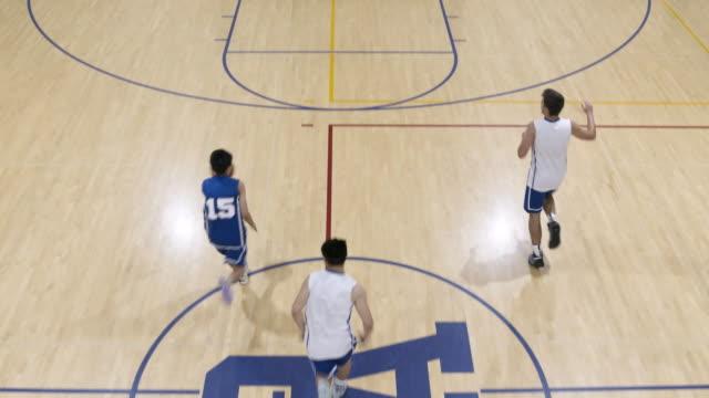 vídeos y material grabado en eventos de stock de tiro de ángulo alto un atleta anota un tiro durante un partido de baloncesto de la high school secundaria - jugador de baloncesto