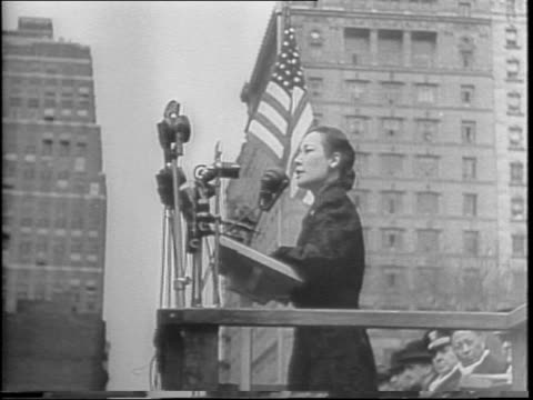 High angle shot of motorcade approaching New York City Hall / large crowd of ChineseAmerican onlookers waving American and Chinese flags / woman with...