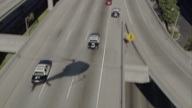 High angle shot of police cars chasing a car on a freeway in Los Angeles.