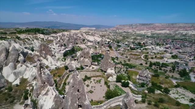 vídeos de stock e filmes b-roll de high angle shot of rocky hills and rural town - exposto ao ar
