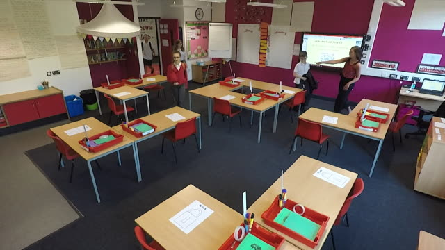 high angle shot of schoolchildren entering classroom that is set up in a socially distanced manner as some year groups return to school as... - primary school child stock videos & royalty-free footage