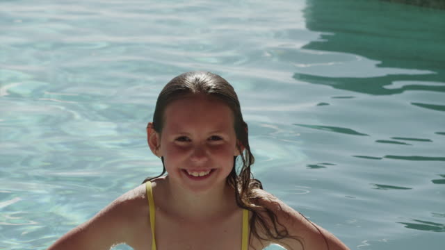 high angle shot of smiling girl in swimming pool / cedar hills, utah, united states - piscina pubblica all'aperto video stock e b–roll