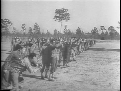 high angle shot of soldiers practicing combat exercises in field / soldiers throw one another to the ground over their shoulders then run and clap in... - 自重トレーニング点の映像素材/bロール